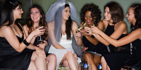 Friends drinking cocktails with bride in nightclub
